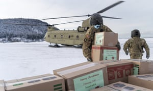 Soldiers unload gifts from a CH-47 Chinook helicopter in Nanwalek, Alaska, during Operation Santa Claus.