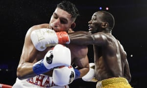 Terence Crawford, right, punches Amir Khan during the fifth round of their WBO world welterweight championship boxing match.