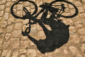 A rider's shadow is cast on cobblestones prior to the start of the ninth stage between Arras and Roubaix