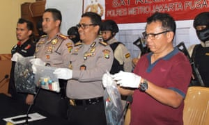 Indonesian police officers display evidence collected during a raid on a gay sauna.