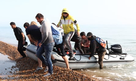 A group of people thought to be migrants arriving in an inflatable boat at Kingsdown beach, near Dover in September.