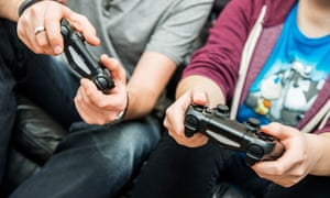 Detail of two people holding Sony PlayStation 4 video game console controllers.