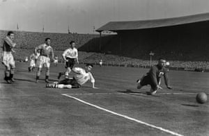 Goalkeeper Stan Hanson turns Mortensen's shot round the post.
