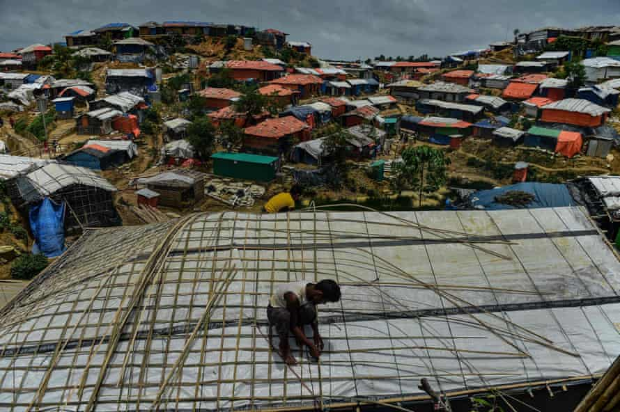 A Rohingya refugee uses bamboo to fix his roof during the monsoon season at Balukhali refugee camp, neighbouring the Kutupalong site, in Cox's Bazar, Bangladesh