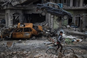 A boy rides his bike past destroyed cars and houses in a neighbourhood recently liberated by Iraqi security forces on the western side of the city, 19 March