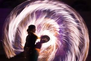 A woman twirls a fire rope