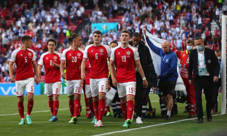 Denmark players escort Christian Eriksen off the pitch in Copenhagen.