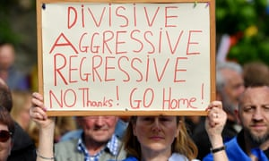 Protester carries a banner reading: 'Divisive, Aggressive, Regressive NO thanks! GO Home' during the Conservative leadership hustings in Perthin July 2019.