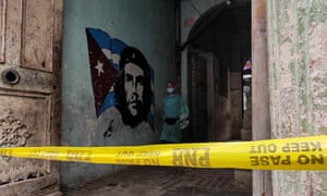 A Covid-19 support personnel walks past a mural depicting revolutionary leader Ernesto Che Guevara in a restricted area after cases of coronavirus were detected in Havana. Cuban authorities announced new measures to control a surge of Covid-19 with increased penalties for people who do not comply with health regulations and campaigns to persuade the population to take the risk more seriously.
