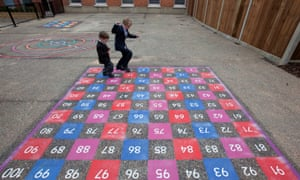 Children playing on a numbered grid in school