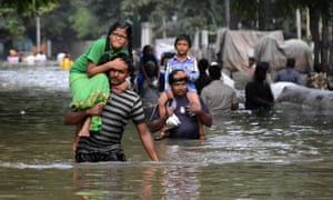 Residents carry children through floodwaters in Chennai.