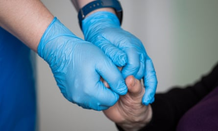 A close up image of a person wearing blue clinical gloves holding the hand of another person