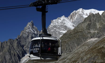 Visitors wear protective masks as they ride the Skyway cable car in front of Mont Blanc in Courmayeur, Italy.