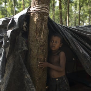 A young Rohingya refugee boy stands under a makeshift shelter in Kutupalong