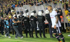 Police officers hold shields to protect Ricardo Quaresma from objects thrown at him by Fenerbahçe fans.