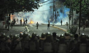 Indonesian riot police officers are seen during a clash in front of the Election Supervisory Agency in Jakarta