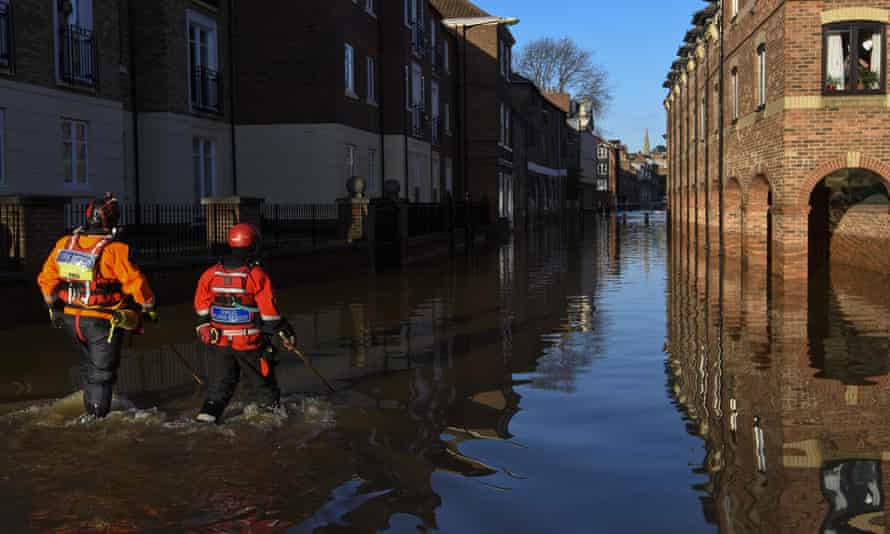 Rescue crews use poles to check the depth of floodwater in York