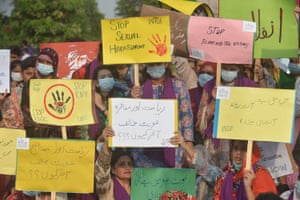 Human rights activists hold placards with palm prints in red or red circles and shout slogans