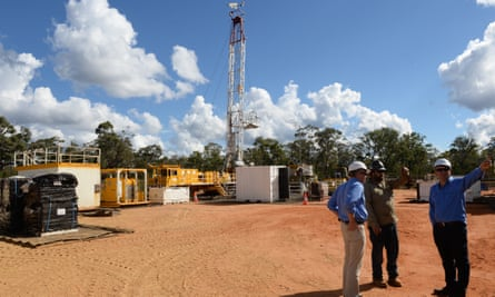 Men with hard hats in front of the Pilliga gas well rig