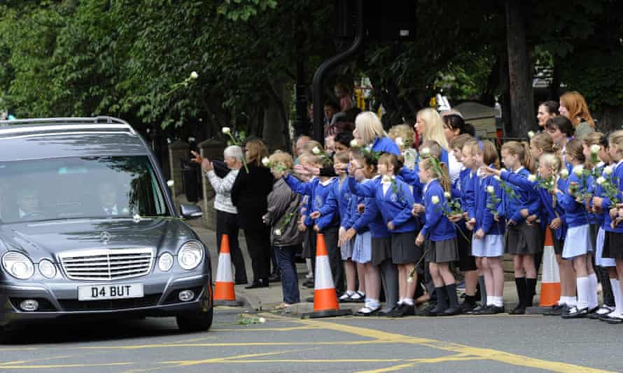 Norristhorpe pupils throw white roses at the cortege.