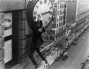 Harold Lloyd hanging from the hands of a large clock, suspended over a busy street, in Safety Last! (1923).