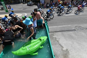 Fans stands in a handcrafted swimming pool next to an inflatable crocodile as riders pass by during the sixteenth stage around Nimes.