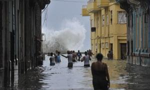 Cubans wade through a flooded street in Havana on Sunday