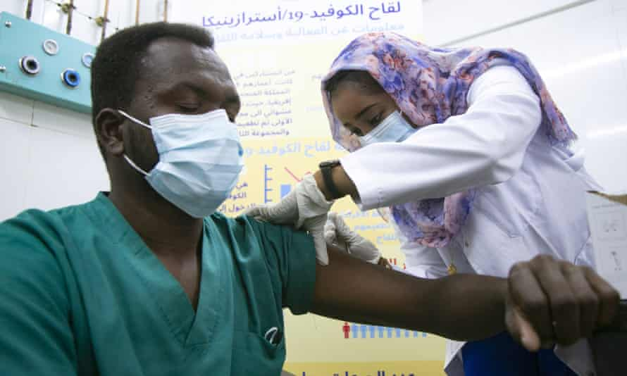 A Sudanese health worker receives a dose of Covid vaccine at Jabra hospital in Khartoum