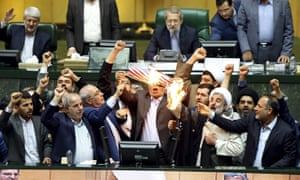 Iranian lawmakers burn two pieces of papers representing the US flag and the nuclear deal in the parliament in Tehran.