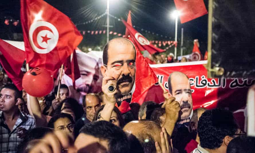 People hold portraits of slain Tunisian lawyer and politician Chokri Belaid, during a demonstration against the Islamist-led government.