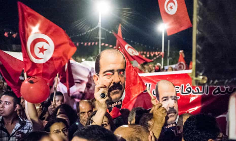 Protesters hold portraits of the slain leftwing politician Chokri Belaid in Tunis, August 2013