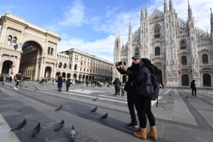 Two people take a selfie in front of the Milan's Cathedral in Milan, Italy, on 25 January 2021. In Italy, the orange zones (medium-high risk) , such as the Lombardy Region, stipulate that shops can open, while restaurants and bars are closed except for takeaway.