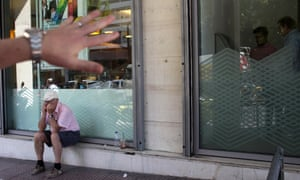 A pensioner sits outside a bank in Athens.