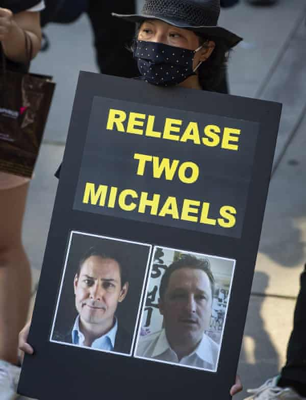 A woman holds a sign with images of Michael Kovrig, left, and Michael Spavor, who have been detained in China since December 2018, during a rally in support of Hong Kong democracy in Vancouver, Canada.