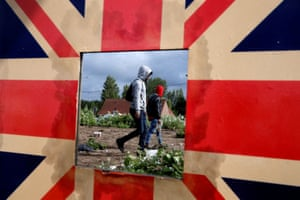 Calais, France Migrants are reflected in a mirror bordered with the union flag as French police officers dismantle a makeshift shelter camp.