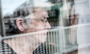 Senior woman looking out through a window