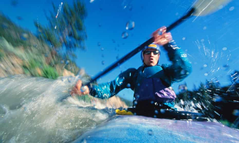 Close up, as water splashes the camera and waves swirl around, of someone doing whitewater kayaking in New Zealand