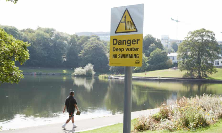 Someone walking past a sign saying 'danger, deep water, no swimming' next to a reservoir