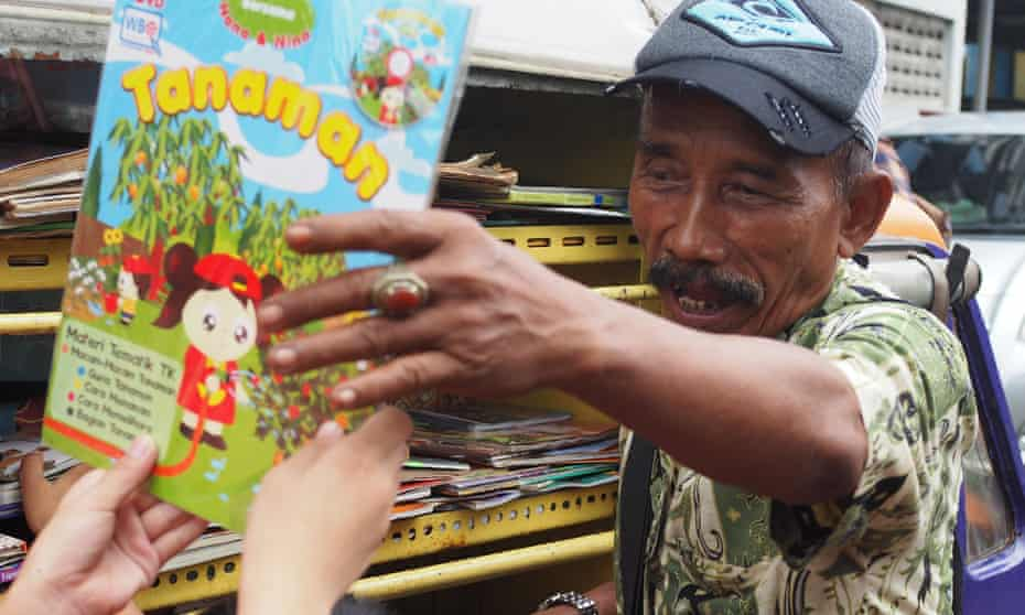A man hands a child a book from his mobile library