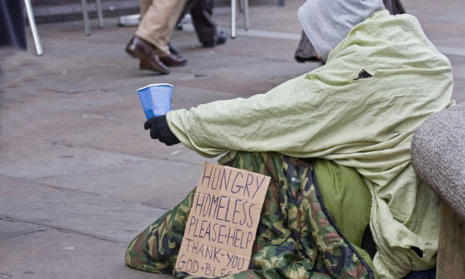 A homeless man begging on a street