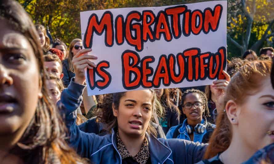 A student holding a 'Migration is beautiful' sign at an anti-Trump rally in New York