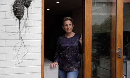 woman with short hair and dark long sleeved top and jeans stands in the doorway of a white walled house
