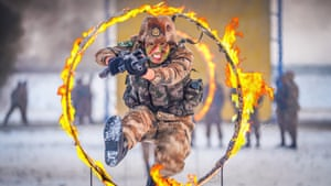 Shihezi, China. A soldier jumps through a circle of fire during a drill