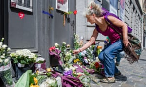 A woman lays flowers at the Jewish Museum in Brussels on 25 May2014 after a terrorist attack in which four people were killed.