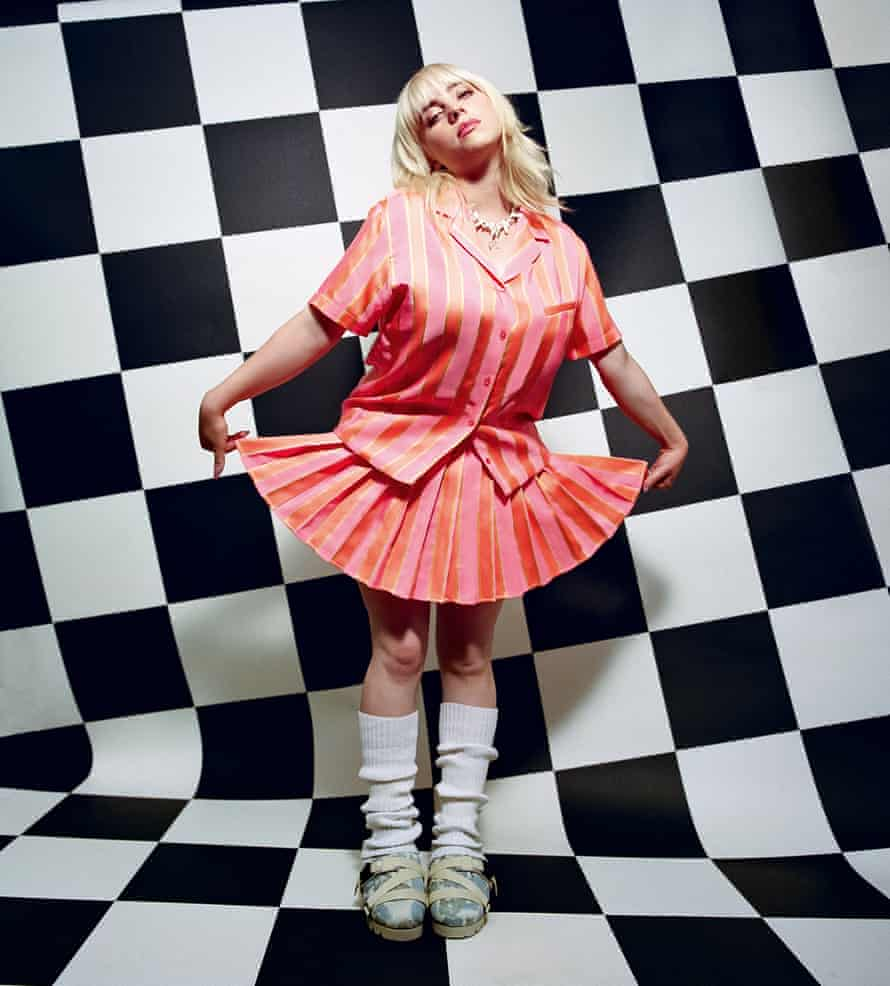 Billie Eilish in pink stripy outfit against black and white checked background