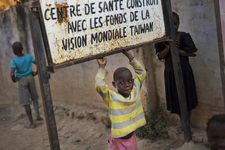 A child plays under a sign at the Mama Wa Mapendo clinic in Lubumbashi, DRC. A study has found children of miners in the area are at higher risk of birth defects.