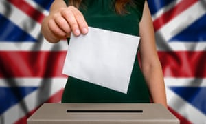 A woman places her vote in a British ballot box.