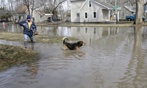 Trino Nuno and his dog Tyson navigate flooded streets in Fremont, Nebraska. Authorities say flooding is so bad that just one highway lane into Fremont remains uncovered.