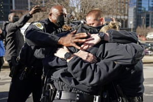 Police Chief John Drake, left, joins a group of police officers as they embrace after speaking at a news conference on Sunday.