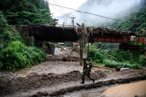 A soldier walks in a area hit by torrential rain in Ashikita